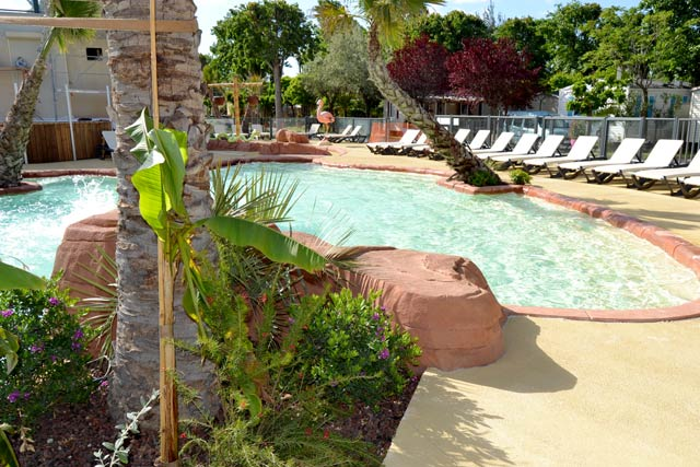 Deckchairs and palm trees as decoration at the pool at the campsite Oasis (...)